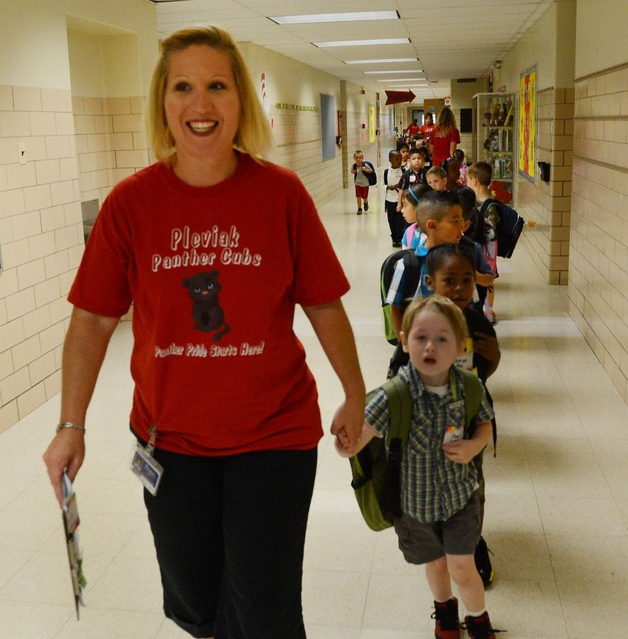 Pleviak Elementary Schoolteacher Patti Hair leads Paul Long and his classmates to their room on the first day of classes for Round Lake Area Unit District's 116 new kindergarten at the building in Lake Villa.