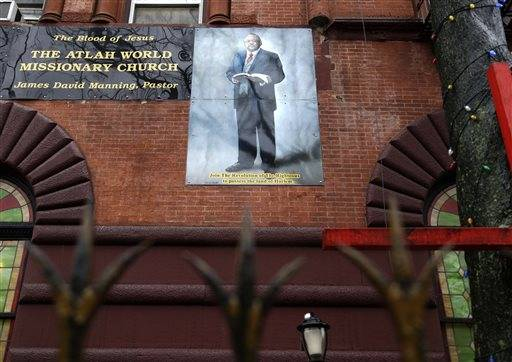 A picture of James Manning, the pastor of Atlah Church, adorns the outside of the building in the Harlem section of New York, Wednesday, Feb. 3, 2016.   Two groups that serve gay New Yorkers are hoping to get the last word on the Atlah World Missionary Church. They want to buy its headquarters at a foreclosure auction. One wants to turn it into housing for gay homeless youth.