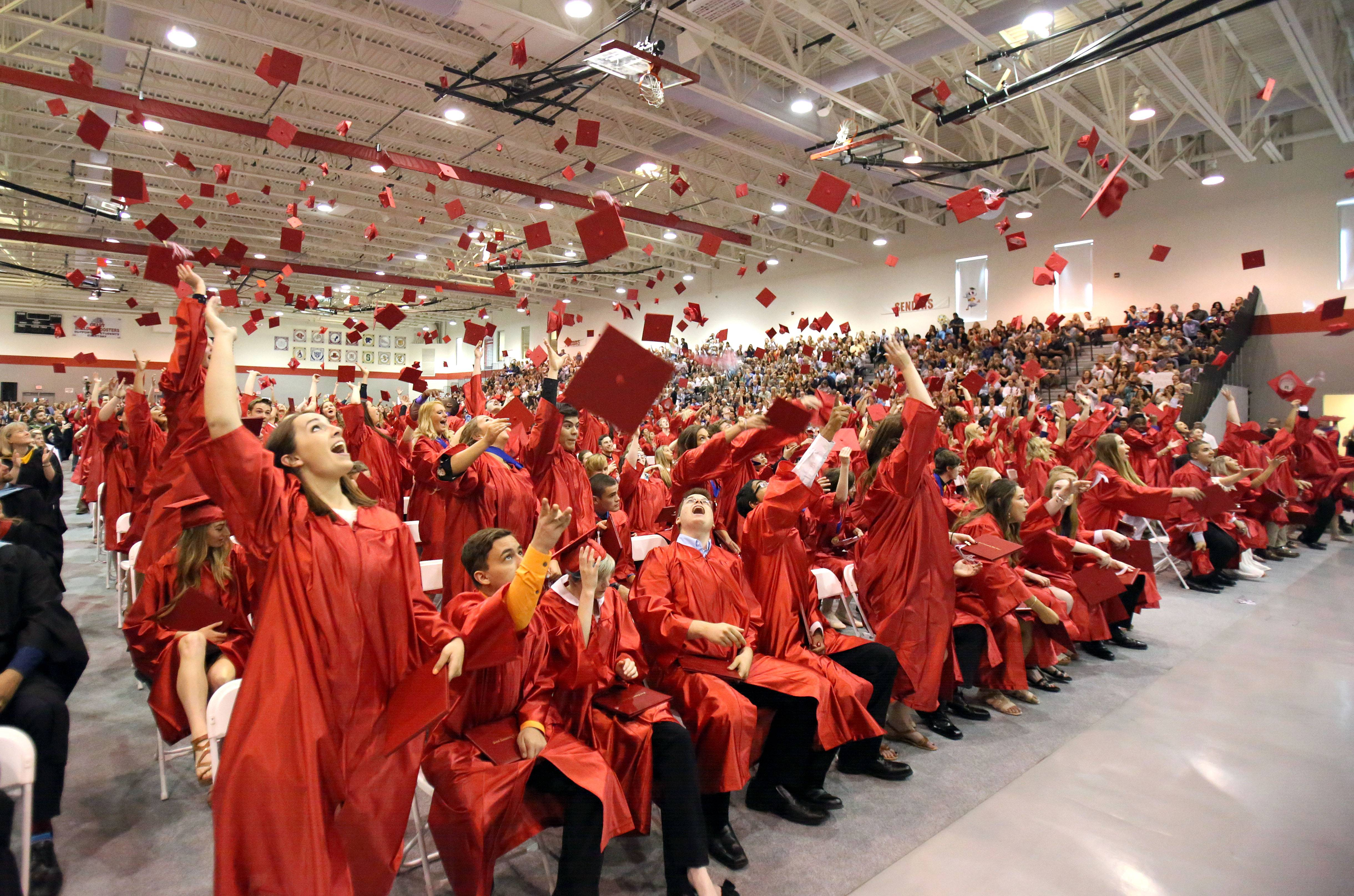 Graduates toss their caps during Grant Community High School's commencement ceremony Sunday in Fox Lake.