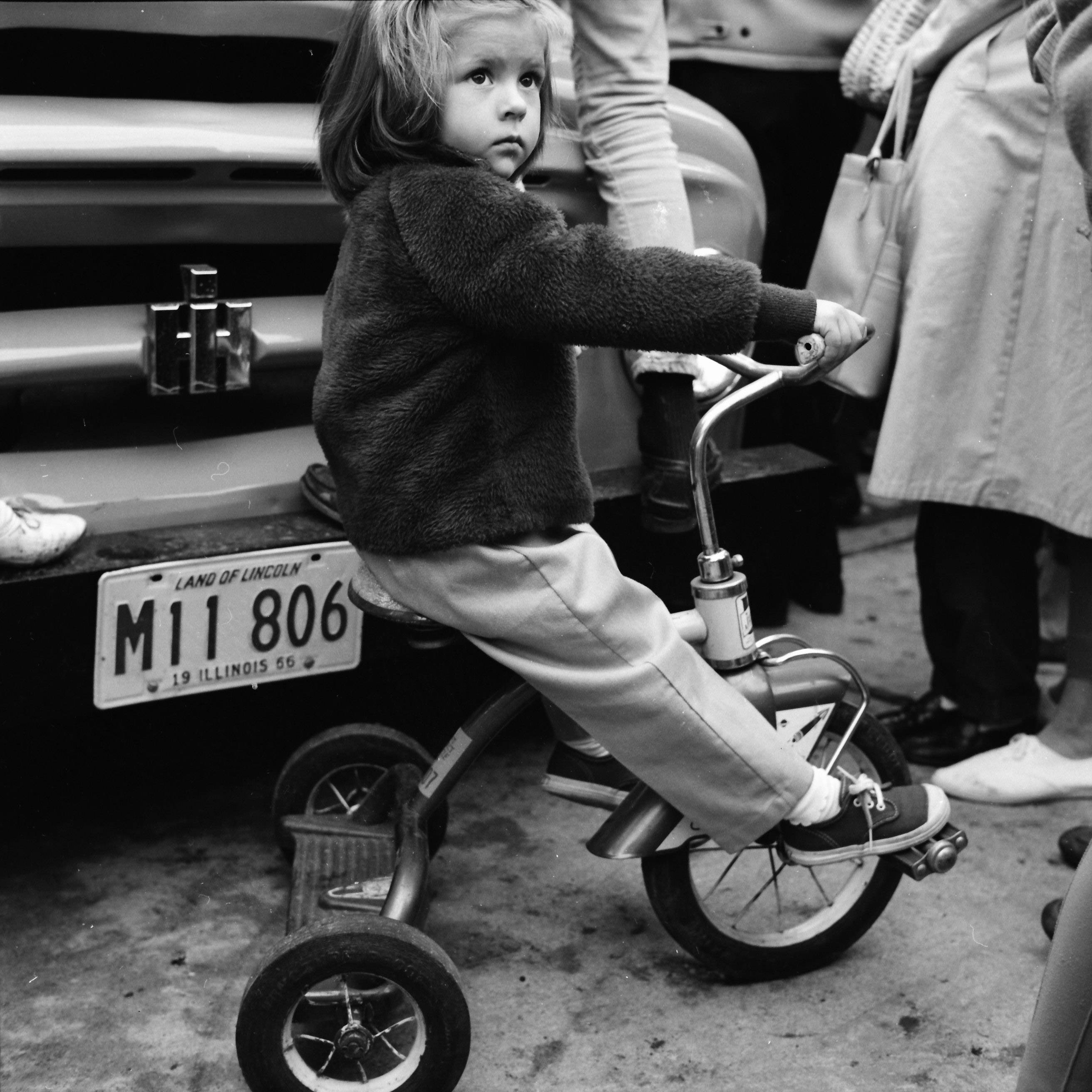 A child tries out a tricycle during a bicycle auction in Mount Prospect.