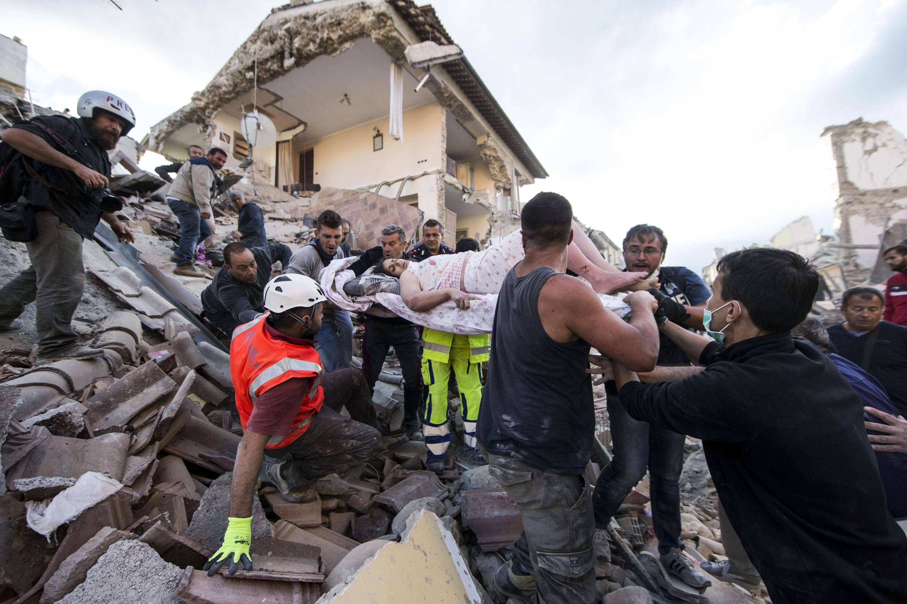 A woman is pulled out of the rubble following an earthquake in Amatrice Italy, Wednesday, Aug. 24, 2016. The magnitude 6 quake struck at 3:36 a.m. (0136 GMT) and was felt across a broad swath of central Italy, including Rome where residents of the capital felt a long swaying followed by aftershocks.