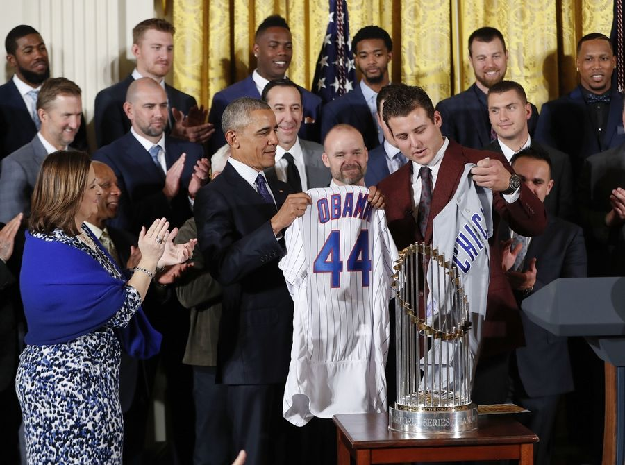 President Barack Obama holds up a personalized Chicago Cubs baseball jersey presented to him by Anthony Rizzo, right, during a ceremony Monday in the East Room of the White House in Washington.