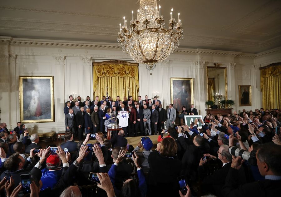 President Barack Obama holds up a personalized Chicago Cubs baseball jersey presented to him during a ceremony Monday in the East Room of the White House in Washington.