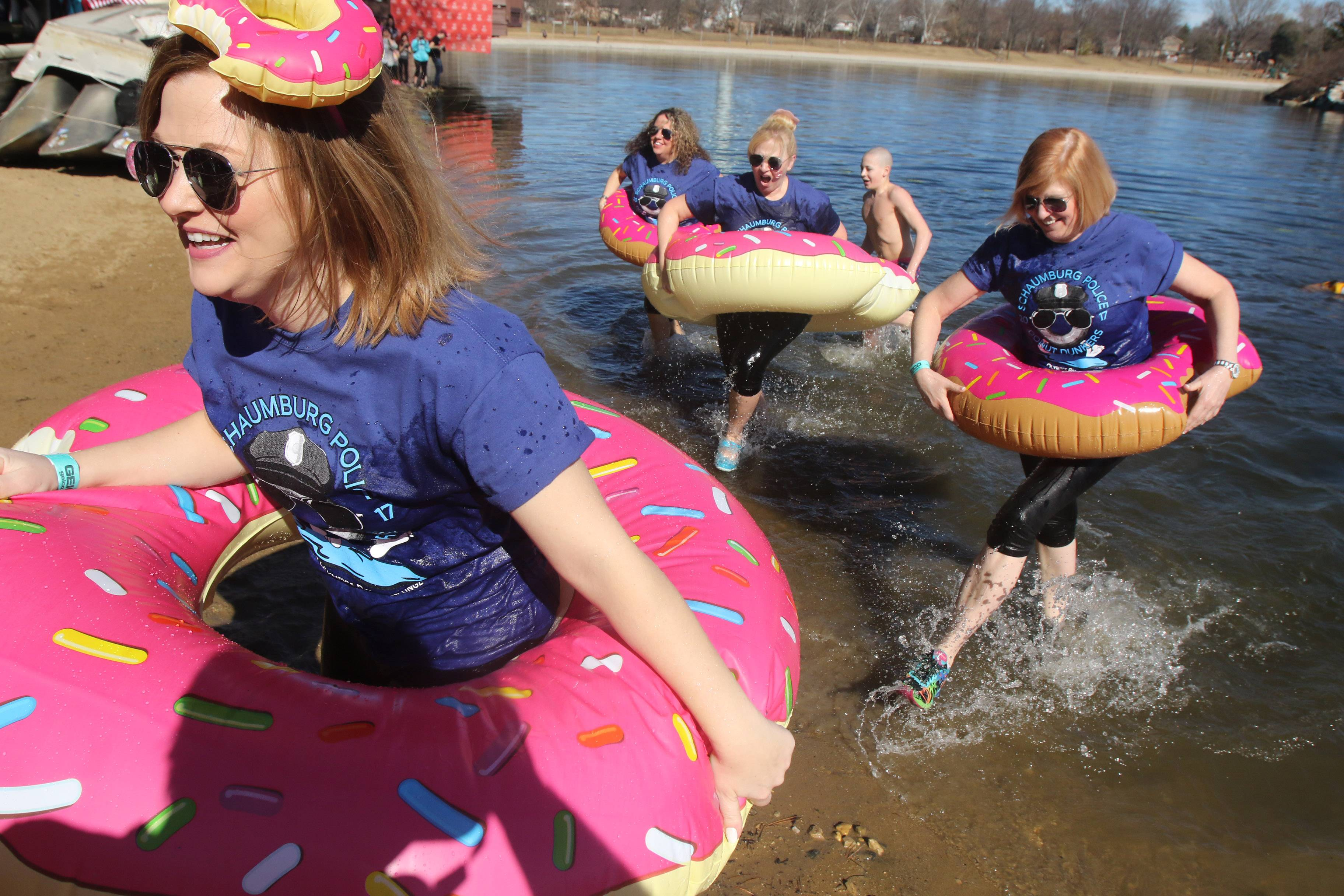 Members of the Schaumburg Police Donut Dunkers run out of the water after participating in the Palatine Polar Plunge on Sunday at Twin Lakes Recreation Area on a spring like afternoon. More than 350 plungers participated in the Law Enforcement Torch Run event that supports Special Olympics.
