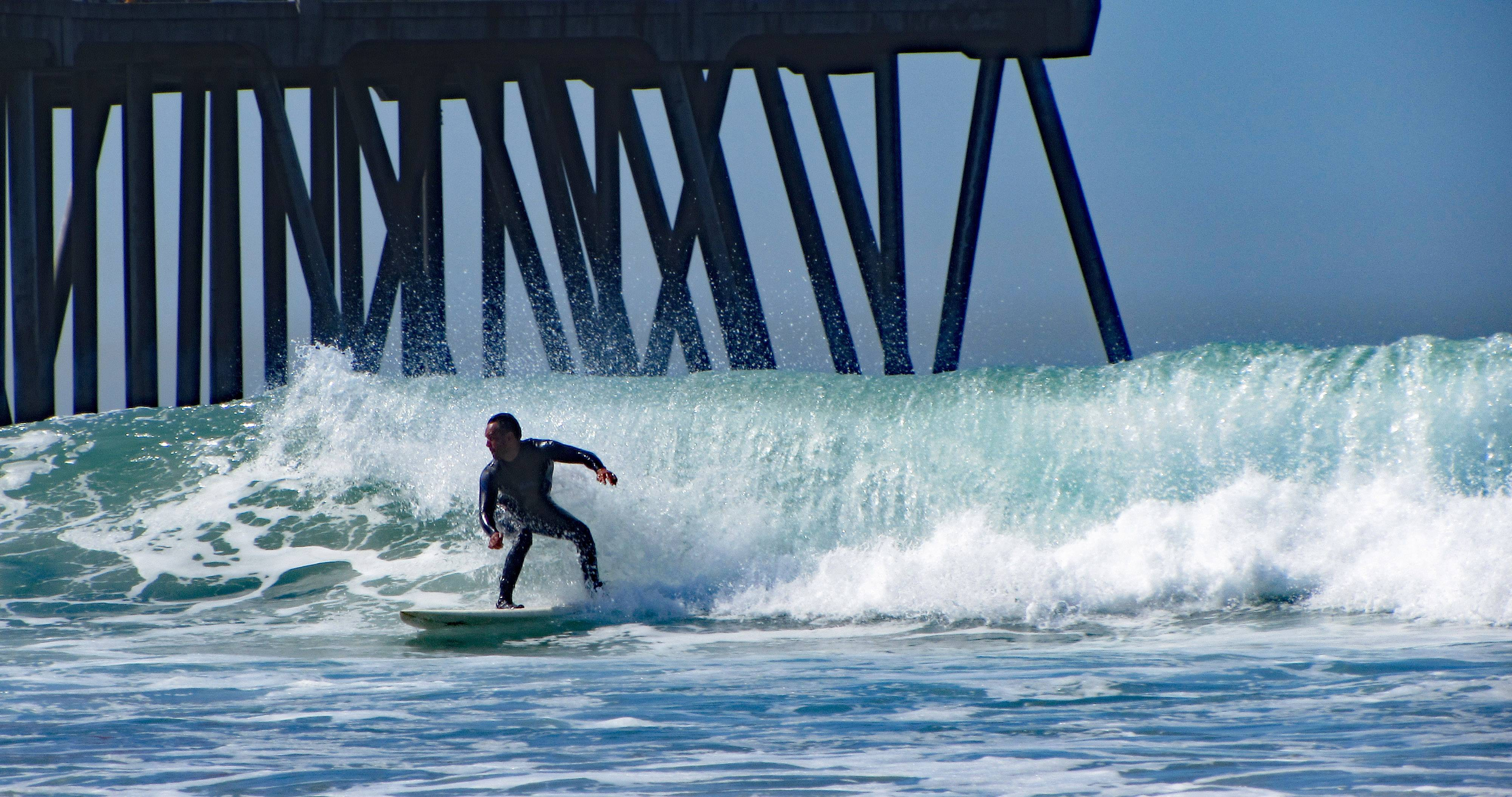 A surfer shoots past the pier on a sweeping wave at Huntington Beach, California on March 26, 2015.