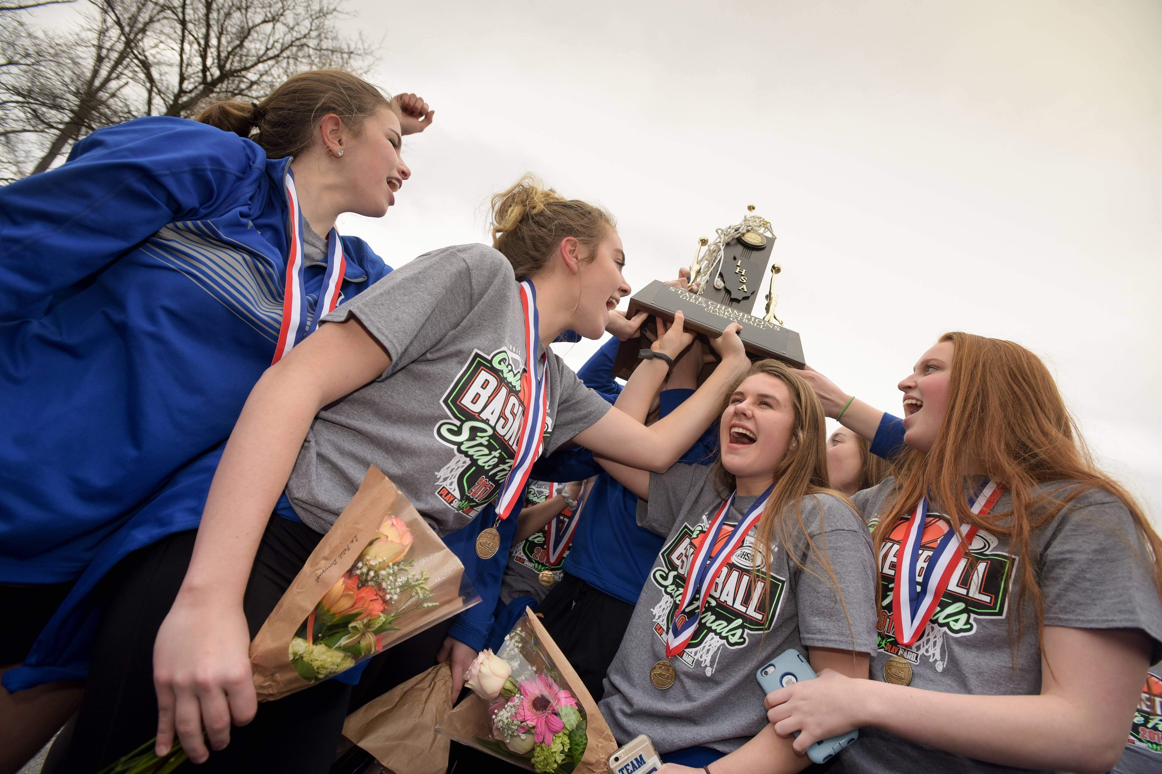 Geneva High School girls basketball team celebrates with their championship trophy after winning the state championship on Saturday.