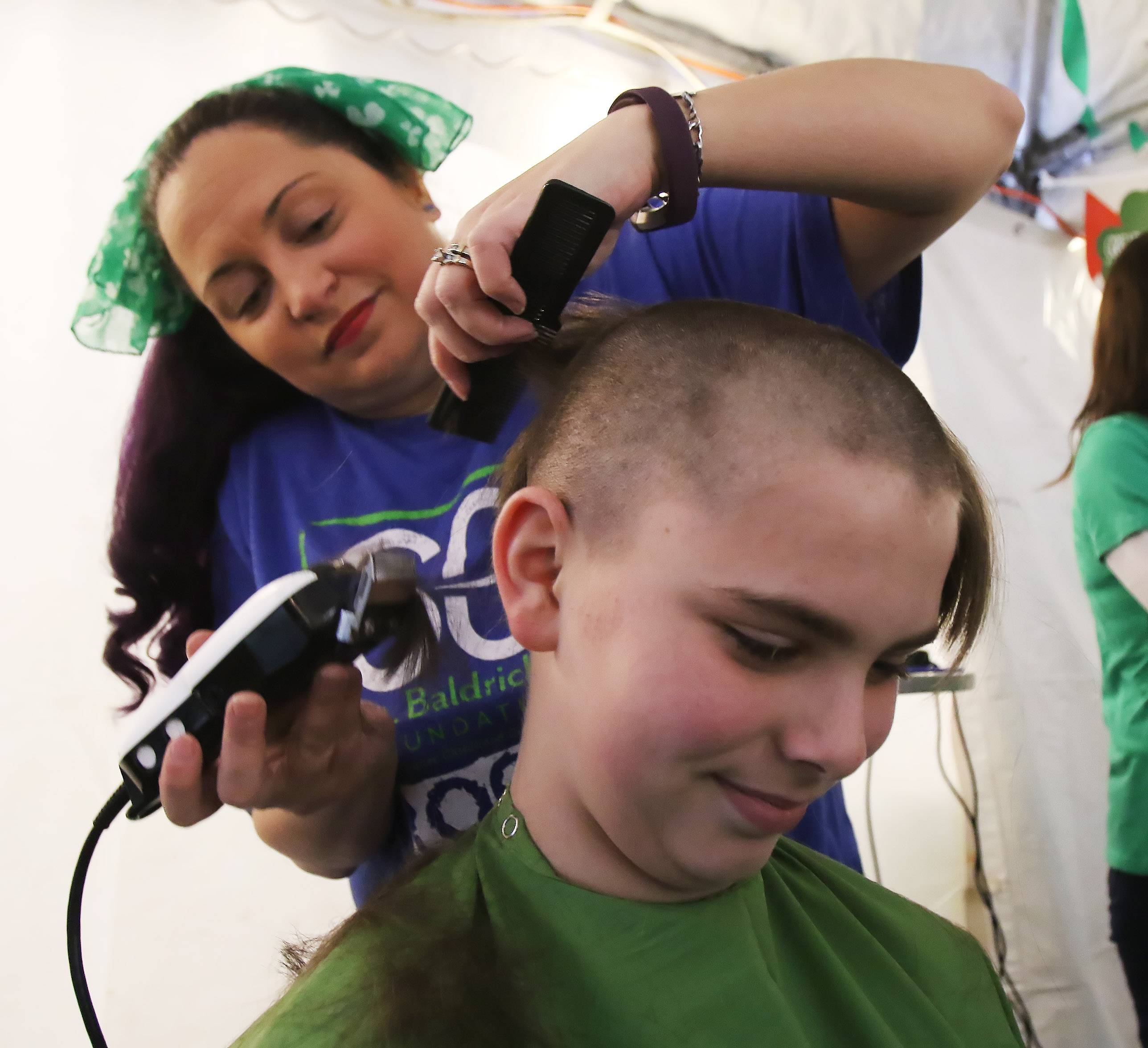 Thirteen-year-old Ryan Siegel of Lake Zurich gets his head shaved by Shelly Healy of Volo during the St. Baldrick's shaving event Sunday in Wauconda to help find a cure for children's cancer. More than 75 people were expected to have their heads shaved at the charity event.