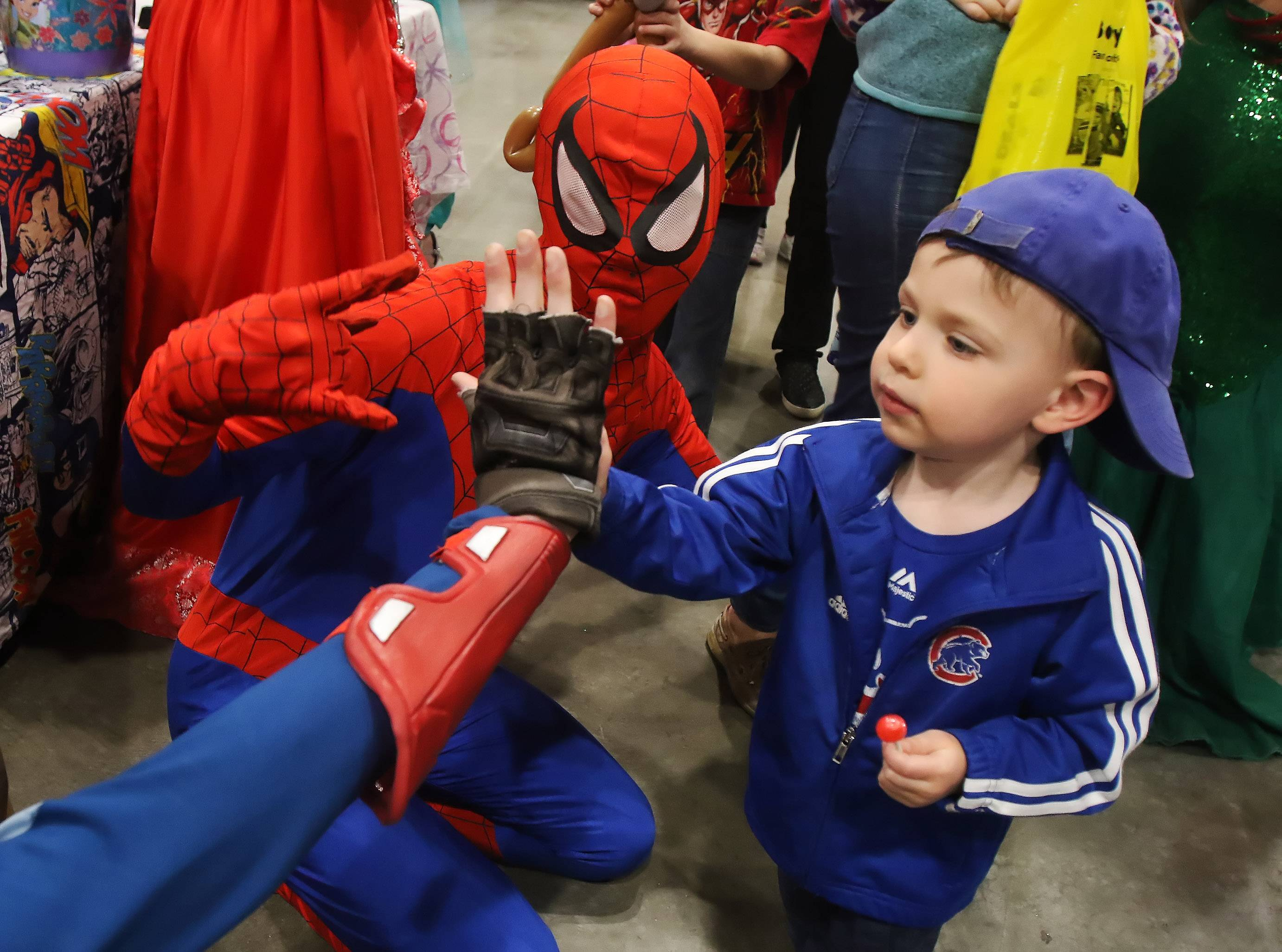 Lucas Duffy, 2, of Dundee Township slaps hands with Captain America, played by Alex Rogers and Spiderman, played by Joe Franzen, of Kids Kustom Parties in Palatine during the 12th annual Kids Expo on Sunday at the Schaumburg Convention Center. The Family Time Magazine event featured live animals, costumed characters, inflatable bouncers, miniature golf and more.