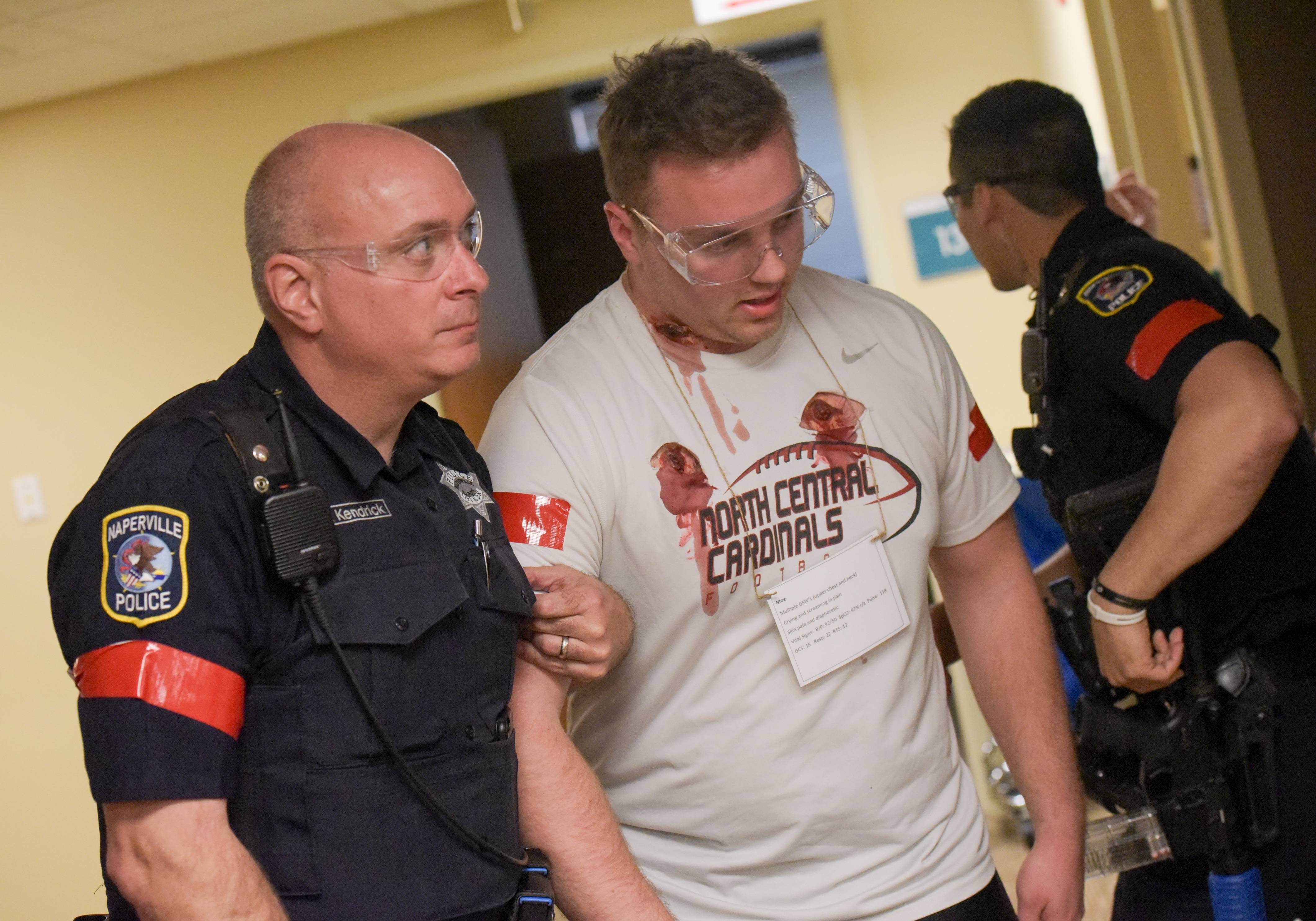 A man acting as a victim Thursday morning during an active shooter drill at Edward Hospital in Naperville is helped out of danger by a Naperville police officer.