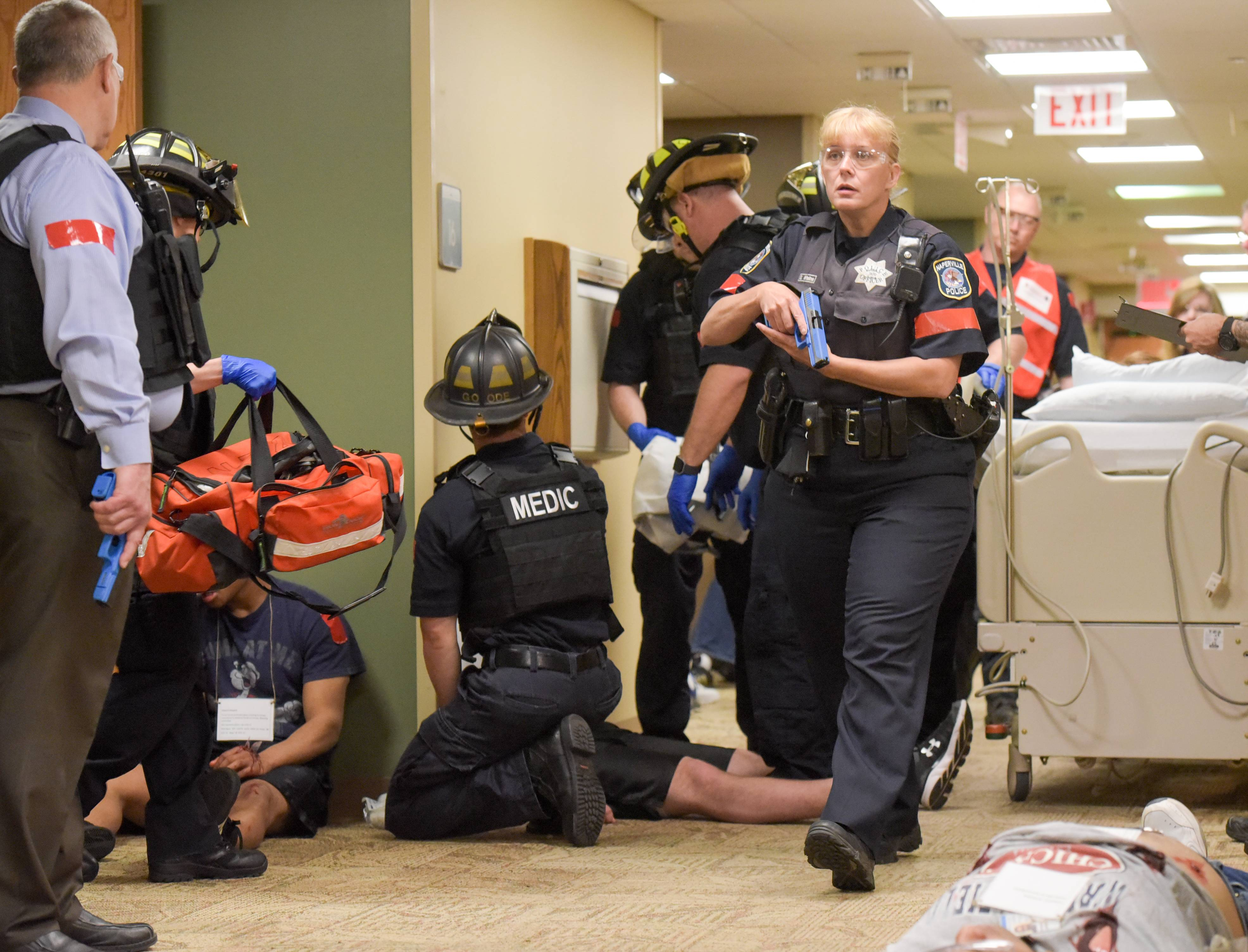 Naperville officers secure the scene as paramedics tend to actors pretending to be injured during an active shooter drill.