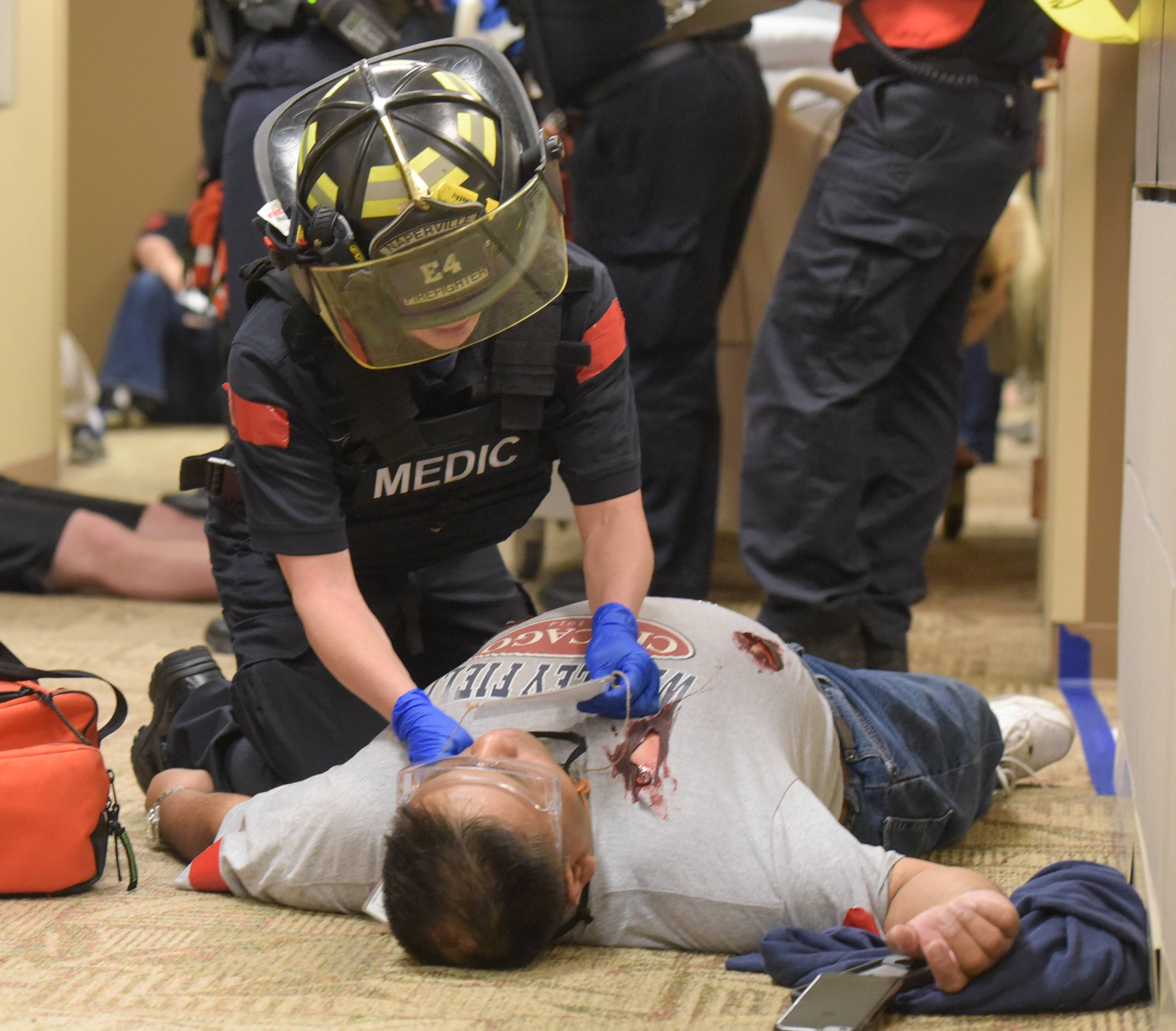 A Naperville paramedic in a ballistic vest and helmet checks on a victim during an active shooter drill Thursday morning at Edward Hospital.
