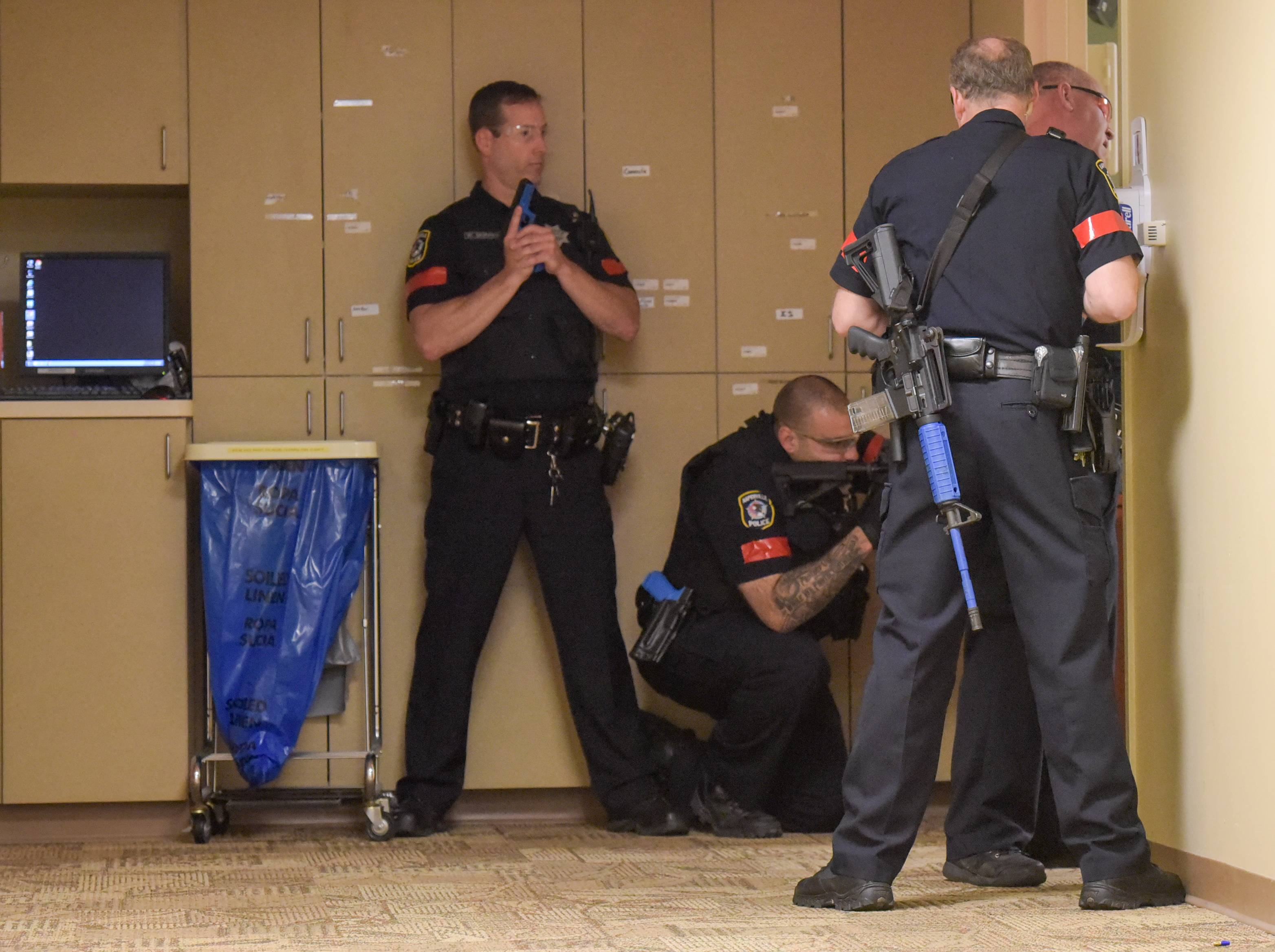 Naperville police guard the door of a hospital room where the suspect had barricaded himself in an active shooter drill Thursday morning at Edward Hospital.