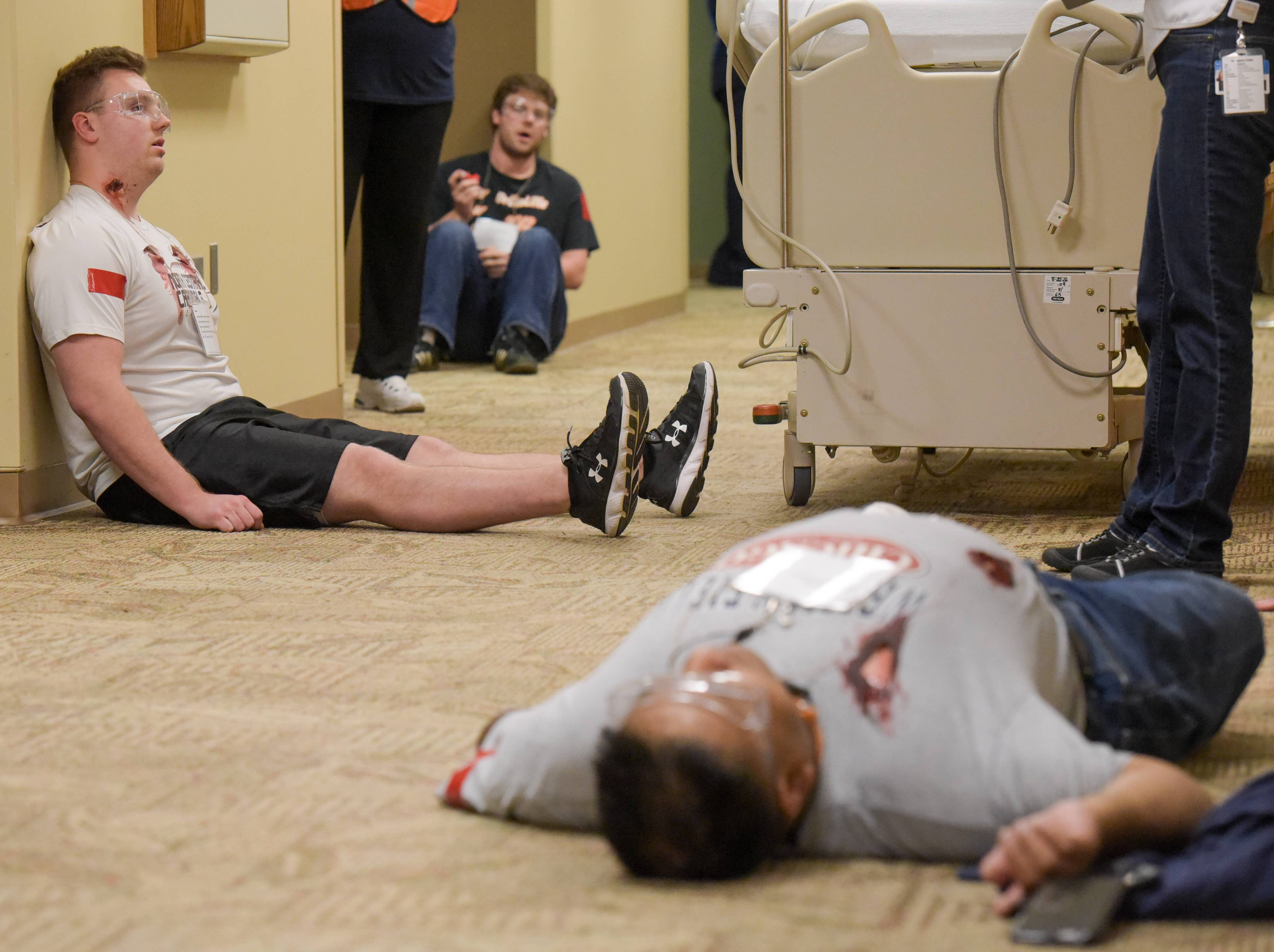 Actors playing victims during an active shooter drill slump across the hallway of a unit on the first floor.