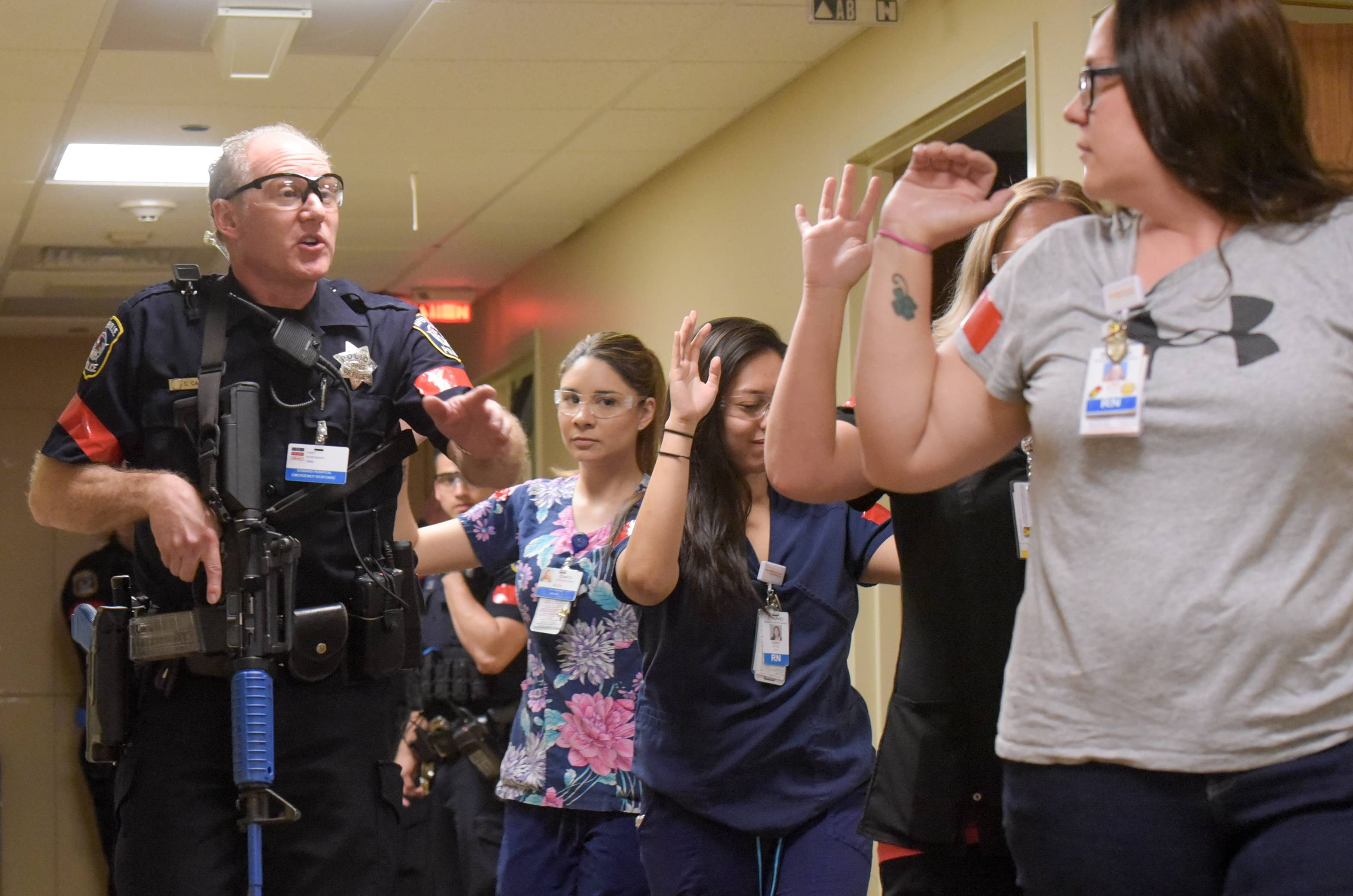 Naperville police escort hospital employees out of the unit affected by an active shooter drill Thursday morning.