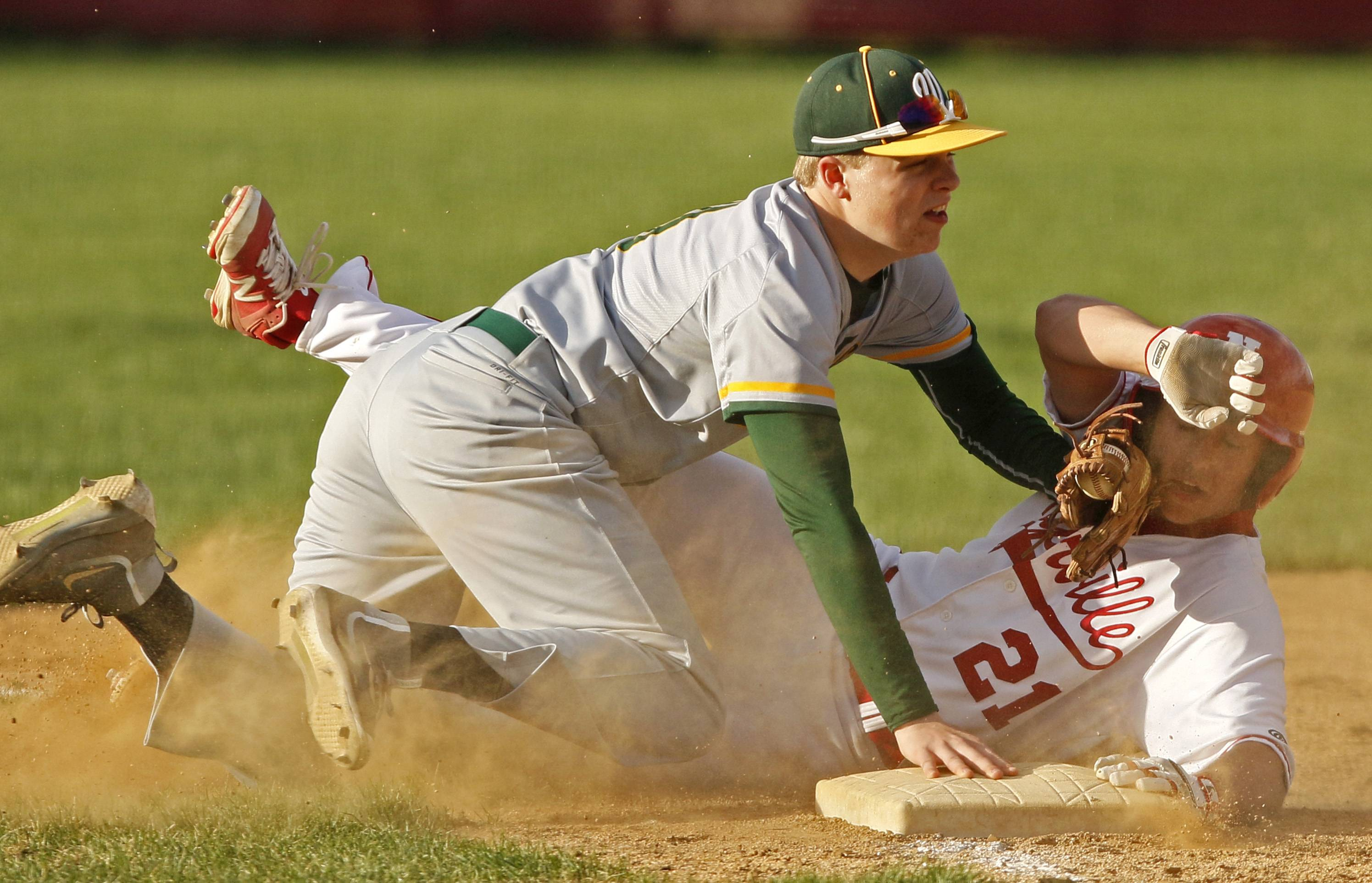 Waubonsie Valley third baseman Jacob Vandrie tags out Naperville Central's Joshua Boomgarden (21).