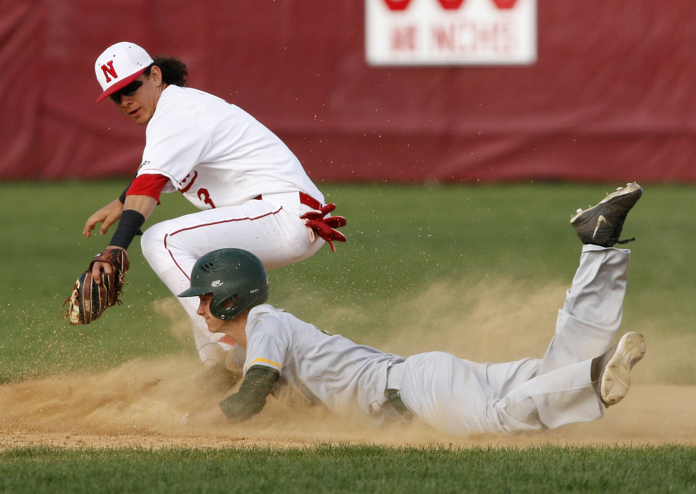 Waubonsie Valley's Eric Esch slides safely into second base under the tag of Naperville Central's Gabe Soria.