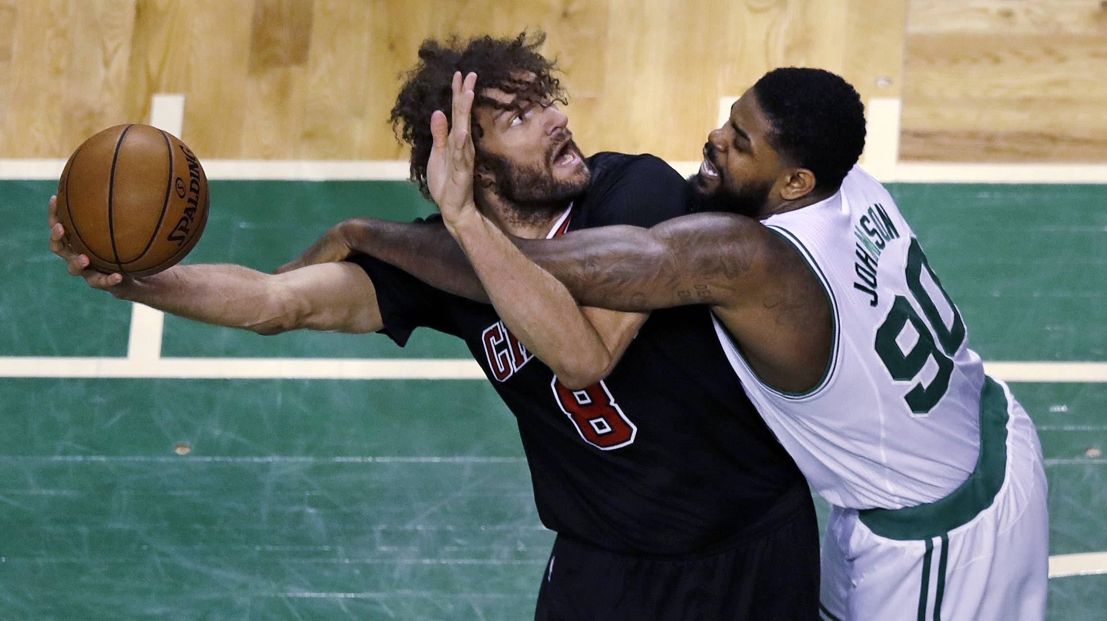 Boston Celtics forward Amir Johnson (90) fouls Chicago Bulls center Robin Lopez (8) during the first quarter of a first-round NBA playoff basketball game in Boston, Tuesday, April 18, 2017.
