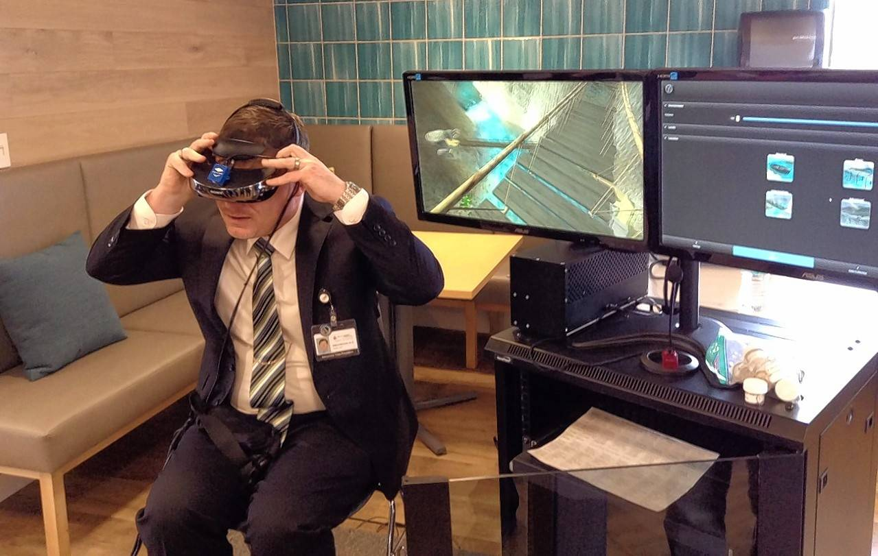 Patrick McGrath, Amita Health assistant vice president of residential services, demonstrates a virtual reality program of a rickety bridge over a river to help people with an intense fear of heights during the dedication and tour of the new Foglia Family Foundation Residential Treatment Center in Elk Grove Village Friday.