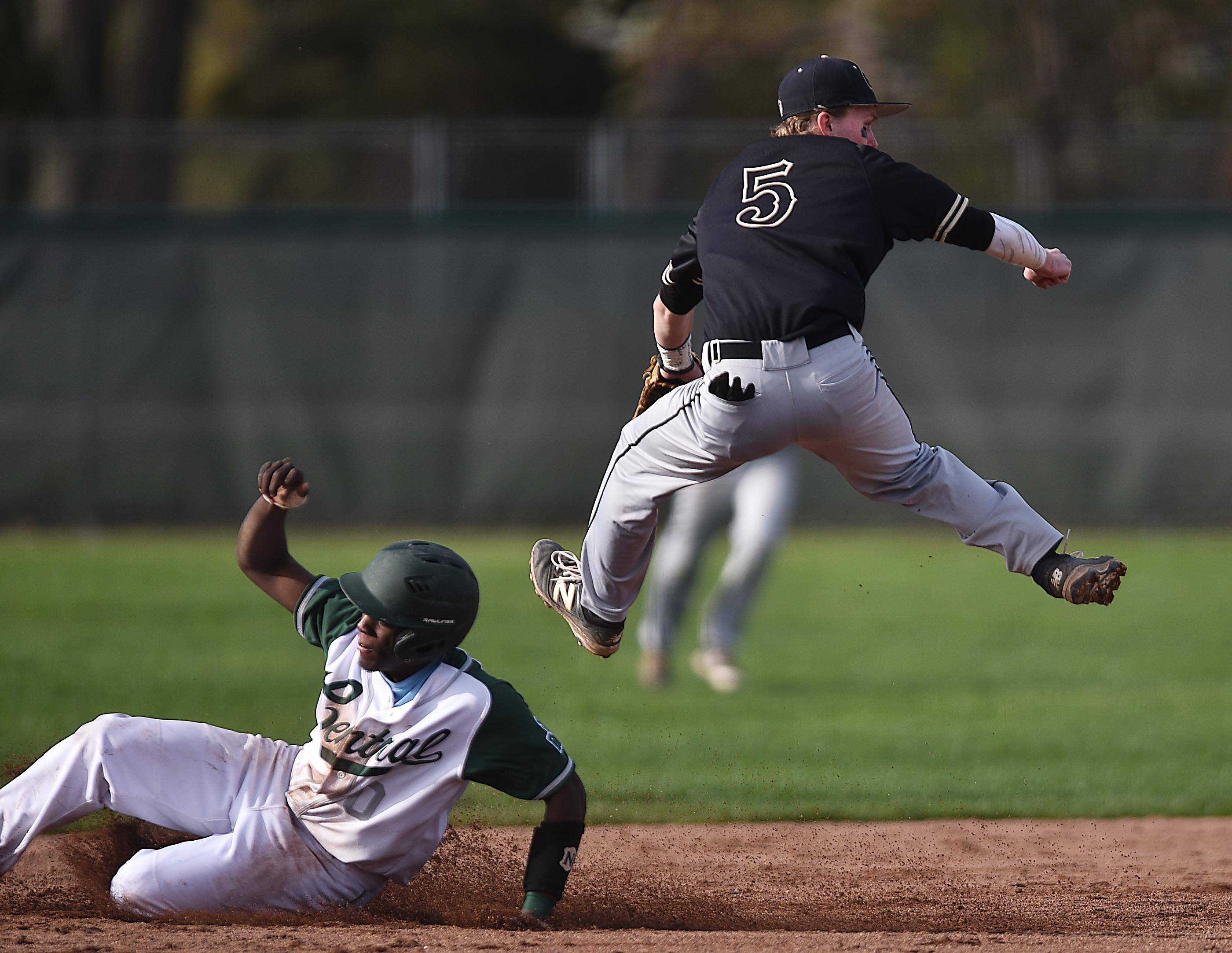 Grayslake Central pinch runner Xavier Hunter is forced out by Grayslake North's Declan Peterson, who leaps over him and completes the double play to end the second inning Friday at Grayslake Central.