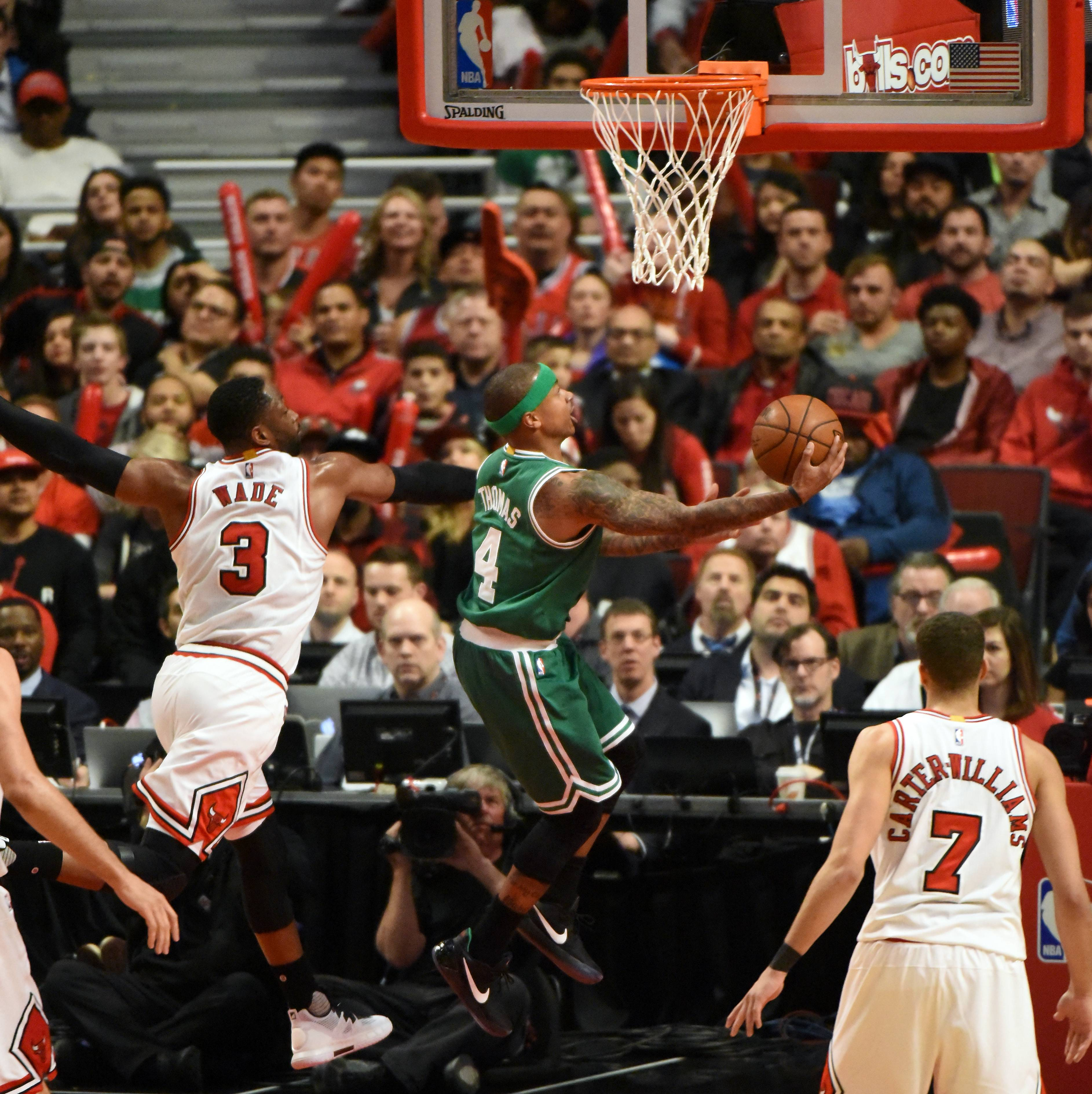 Boston Celtics guard Isaiah Thomas (4) slides to the hoop past Chicago Bulls guard Dwyane Wade (3) Friday at the United Center in Chicago.