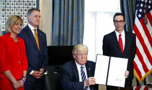 President Donald Trump, accompanied by, from left, Rep. Claudia Tenney, R-N.Y., Sen. David Perdue, R-Ga., and Treasury Secretary Steve Mnuchin, holds up a signed Executive Order, Friday, April 21, 2017, at the Treasury Department in Washington. (AP Photo/Alex Brandon)