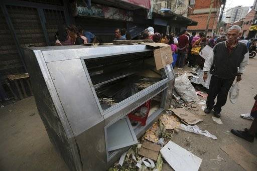 A pedestrian stands next to a refrigerator destroyed in a night of looting, in El Valle neighborhood in Caracas, Venezuela, Friday, April 21, 2017. At least 12 people were killed overnight following looting and violence in Venezuela's capital amid a spiraling political crisis, authorities said Friday. Most of the deaths took place in El Valle, a working class neighborhood near Caracas' biggest military base where opposition leaders say a group of people were hit with an electrical current while trying to loot a bakery protected by an electric fence. (AP Photo/Fernando Llano)