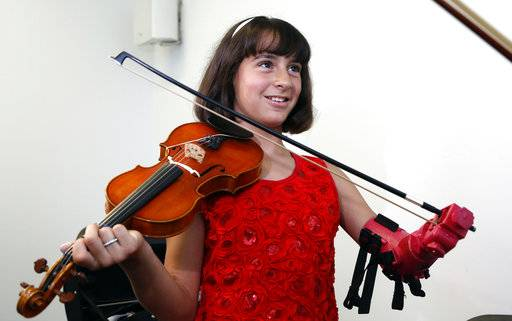 "Ten-year-old Isabella Nicola Cabrera smiles after playing her violin with her new prosthetic at the engineering department of George Mason University in Fairfax, Va., Thursday, April 20, 2017. ""Oh my gosh, that's so much better,"" Isabella said as she tried out the new prosthetic. (AP Photo/Steve Helber)"