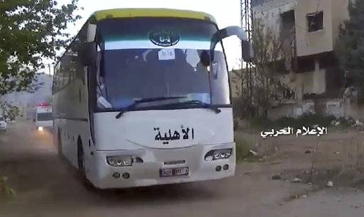 "This frame grab from video provided by the government-controlled Syrian Central Military Media, shows buses carrying opposition fighters leaving Zabadani, near Damascus, Syria, Wednesday, April. 19, 2017, heading toward the northern rebel-held Idlib province. Syria's military media says the evacuation and transfer of thousands of Syrians from four besieged areas has resumed. Logo in Arabic reads, ""Millitary Media.""  (Syrian Central Military Media, via AP)"