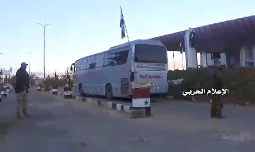 "This frame grab from video provided by the government-controlled Syrian Central Military Media, shows buses carrying opposition fighters leaving Zabadani through a checkpoint, near Damascus, Syria, Wednesday, April. 19, 2017, heading toward the northern rebel-held Idlib province. Syria's military media says the evacuation and transfer of thousands of Syrians from four besieged areas has resumed. Logo in Arabic reads, ""Millitary Media.""  (Syrian Central Military Media, via AP)"