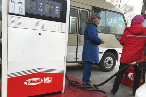 FILE - In this Feb. 22, 2016, file photo, a customer talks to a gas station attendant in Pyongyang, North Korea. Car users in Pyongyang are scrambling to fill up their tanks as gas stations limit services and close their gates amid concerns of a possible shortage. The cause of the restrictions or how long they might last were not immediately known.