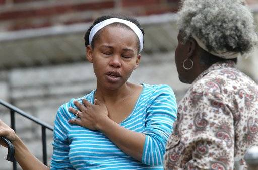 CORRECTS FIRST NAME TO MANYIKA  Manyika McCoy, left, cries while she talks to her mother Alice Spann, Thursday, April 20, 2017, in St. Louis. McCoy had just been talking to two Laclede Gas Co. workers just before they were killed by a man who walked up and started shooting. (J.B. Forbes/St. Louis Post-Dispatch via AP)