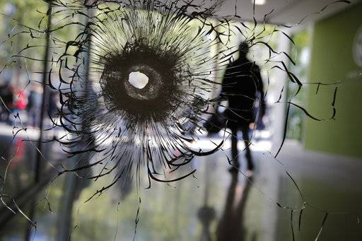 A bullet hole is pictured on a shopwindow of the Champs Elysees boulevard in Paris, Friday, April 21, 2017. France began picking itself up Friday from another deadly shooting claimed by the Islamic State group, with President Francois Hollande convening the government's security council and his would-be successors in the presidential election campaign treading carefully before voting this weekend.