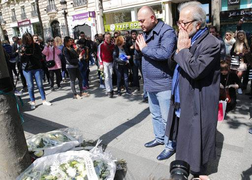 People react at the place where a police officer was killed Thursday on the Champs Elysees boulevard, Friday, April 21, 2017 in Paris. The Champs-Elysees gunman who shot and killed a police officer just days before France's presidential election was detained in February for threatening police but then freed, two officials told The Associated Press on Friday.