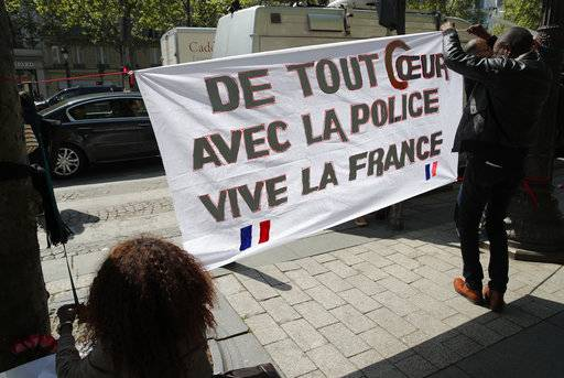 "Three people set up a banner reading ""Our hearts with the police, Long live France"" at the place where a police officer was killed Thursday on the Champs Elysees boulevard, Friday, April 21, 2017 in Paris. The Champs-Elysees gunman who shot and killed a police officer just days before France's presidential election was detained in February for threatening police but then freed, two officials told The Associated Press on Friday."