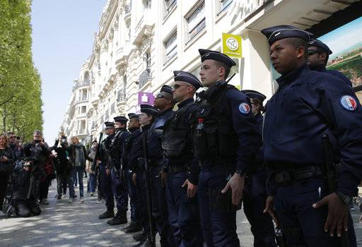 A dozen of police officers stand at attention at the place where a police officer was killed Thursday on the Champs Elysees boulevard, Friday, April 21, 2017 in Paris. The Champs-Elysees gunman who shot and killed a police officer just days before France's presidential election was detained in February for threatening police but then freed, two officials told The Associated Press on Friday.