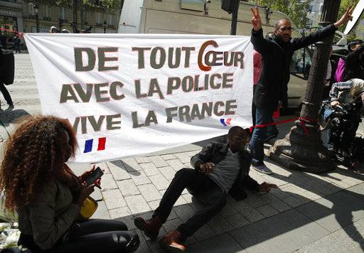"Three people pose by a banner they set up and reading ""Our hearts with the police, Long live France"" at the place where a police officer was killed Thursday on the Champs Elysees boulevard, Friday, April 21, 2017 in Paris. The Champs-Elysees gunman who shot and killed a police officer just days before France's presidential election was detained in February for threatening police but then freed, two officials told The Associated Press on Friday."