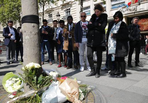 A black ribbon and flowers lay at the place where a police officer was killed Thursday on the Champs Elysees boulevard, Friday, April 21, 2017 in Paris. The Champs-Elysees gunman who shot and killed a police officer just days before France's presidential election was detained in February for threatening police but then freed, two officials told The Associated Press on Friday.