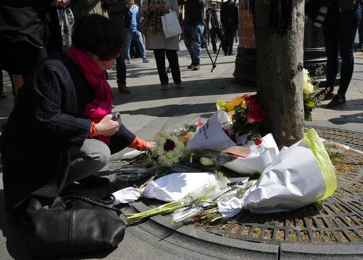 A woman lay flowers at the place where a police officer was killed Thursday on the Champs Elysees boulevard, Friday, April 21, 2017 in Paris. The Champs-Elysees gunman who shot and killed a police officer just days before France's presidential election was detained in February for threatening police but then freed, two officials told The Associated Press on Friday.
