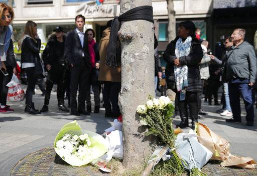 A black scarf hangs on a tree with flowers at the place where a police officer was killed Thursday on the Champs Elysees boulevard, Friday, April 21, 2017 in Paris. The Champs-Elysees gunman who shot and killed a police officer just days before France's presidential election was detained in February for threatening police but then freed, two officials told The Associated Press on Friday.