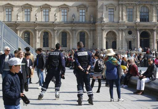 Police officers patrol outside the Louvre museum, Friday, April 21, 2017 in Paris. The shooting at the Champs Elysees rattled France only two days before the end of an unusually suspenseful election contest.