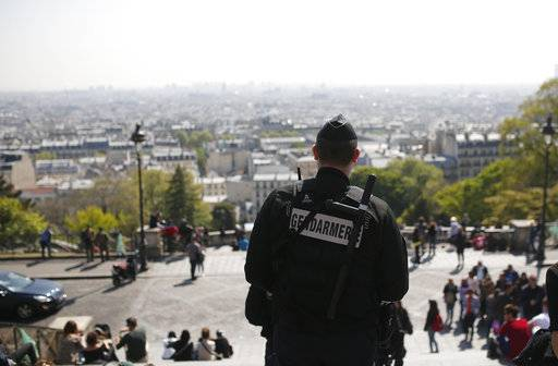 A gendarme patrols in the Montmartre district Friday, April 21, 2017 in Paris. The shooting at the Champs Elysees rattled France only two days before the end of an unusually suspenseful election contest.