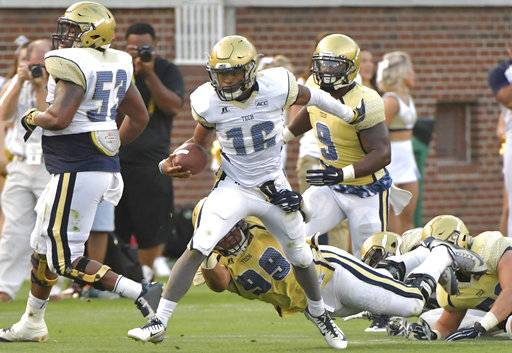 Georgia Tech White Team quarterback TaQuon Marshall (16) runs past Gold Team defensive lineman Desmond Branch (99) during the NCAA college football team's spring game, Friday, April 21, 2017, in Atlanta. (Hyosub Shin/Atlanta Journal-Constitution via AP)