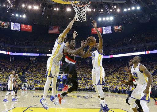 Portland Trail Blazers forward Al-Farouq Aminu, center, shoots between Golden State Warriors center JaVale McGee, left, and forward Kevin Durant (35) during the first half of Game 1 of a first-round NBA basketball playoff series in Oakland, Calif., Sunday, April 16, 2017. (AP Photo/Jeff Chiu)