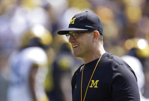 FILE - In this Saturday, April 15, 2017, file photo, Michigan coach Jim Harbaugh watches the NCAA college football team's spring game in Ann Arbor, Mich. Harbaugh's latest, outside-the-box idea is about to take off. Michigan's football team will travel to Rome this weekend and will kick off the unique trip by meeting with refugees before going to the Vatican for a Papal address and practicing a few times. (AP Photo/Carlos Osorio, File)