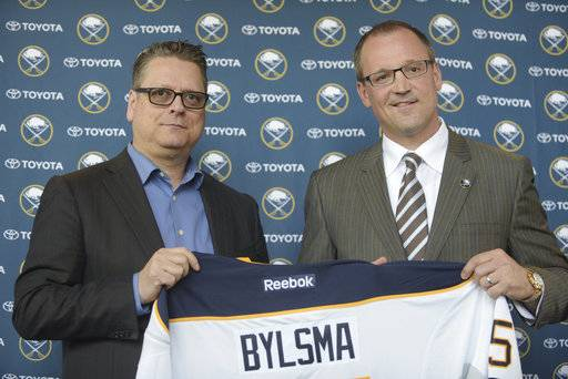 FILE - In this May 28, 2015, file photo, Buffalo Sabres GM Tim Murray, left, and newly hired coach Dan Bylsma hold a Sabres' jersey as they pose for a photo after a news conference in Buffalo, N.Y.  The Sabres have fired general manager Tim Murray and coach Dan Bylsma after the youthful team missed the playoffs for a sixth consecutive season. Owner Terry Pegula made the announcement Thursday, April 20, 2017.