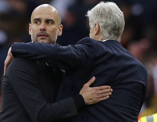 FILE - This is a Sunday, April 2, 2017 file photo of Manchester City manager Pep Guardiola, left, with  Arsenal team manager Arsene Wenger as they embrace each other at the end of the English Premier League soccer match between Arsenal and Manchester City at the Emirates stadium in London. Guardiola's realistic ambitions of capturing the English Premier League title were extinguished weeks ago. Guardiola's last hope of winning silverware in his first season at Manchester City rests with the FA Cup when they play in the semifinal against Arsenal on Sunday April 23, 2017 .