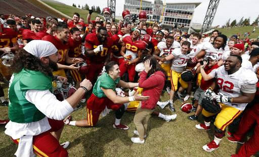 FILE - In this April 8, 2017, file photo, Iowa State quarterback Kyle Starcevich, center, proposes to his girlfriend Tori Monroe, at the end of his team's annual NCAA spring football game, in Ames, Iowa. The increasing visibility of spring football games has offered plenty of feel-good moments and fan-friendly opportunities. What they don't provide is much insight into what these teams will be doing this fall.