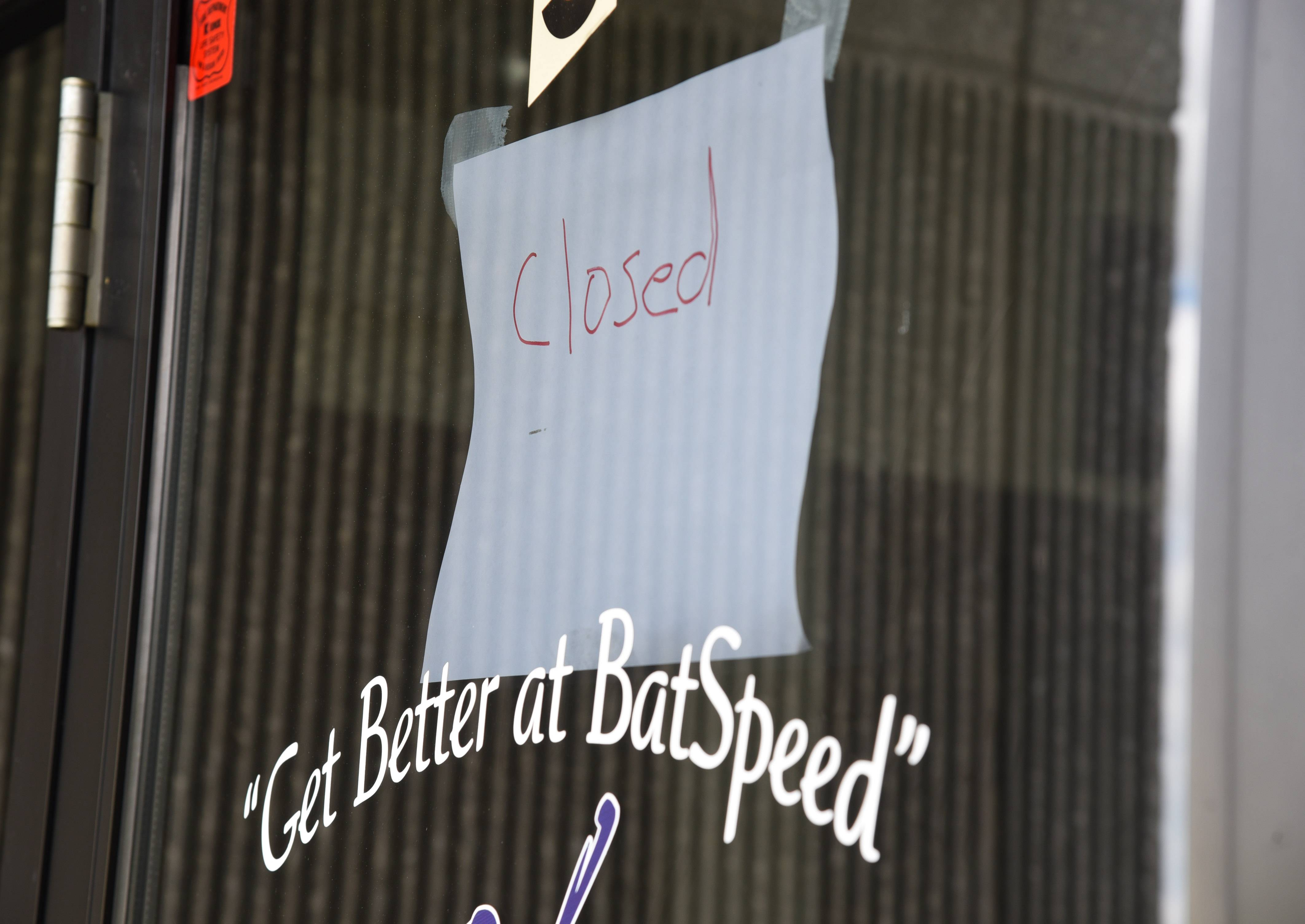 "A handwritten ""closed"" sign is taped to the door at BatSpeed training facility in Gurnee."