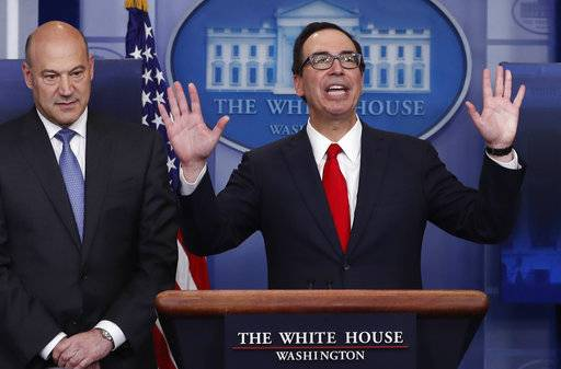 Treasury Secretary Steven Mnuchin, right, joined by National Economic Director Gary Cohn, speaks in the briefing room of the White House in Washington, Wednesday, April 26, 2017. President Donald Trump is proposing dramatically reducing the taxes paid by corporations big and small in an overhaul his administration says will spur economic growth and bring jobs and prosperity to the middle class. (AP Photo/Carolyn Kaster)