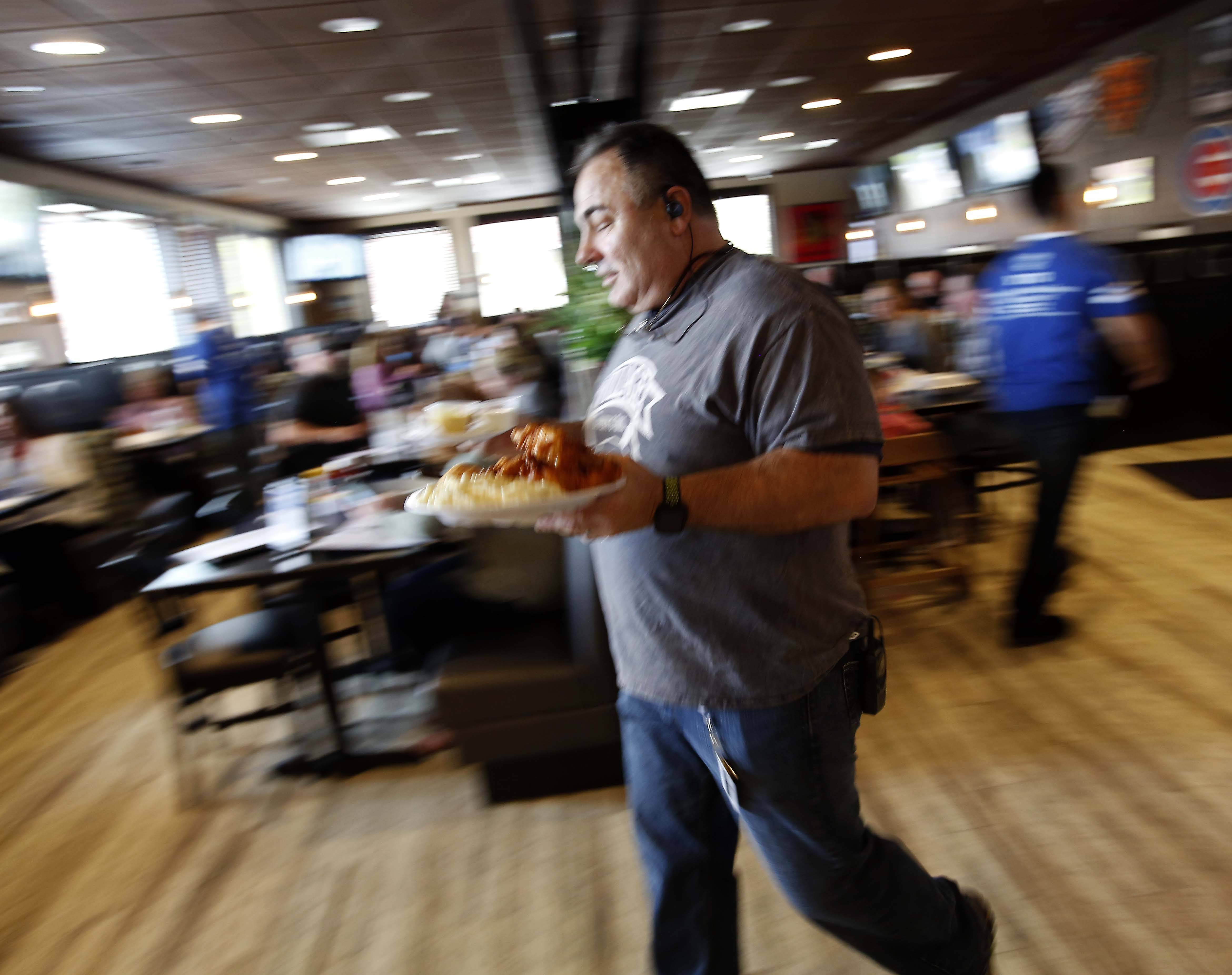 Village Tavern & Grill owner J.R. Hutson celebrates the store's South Elgin opening Thursday by rushing a lunch order to a customer.